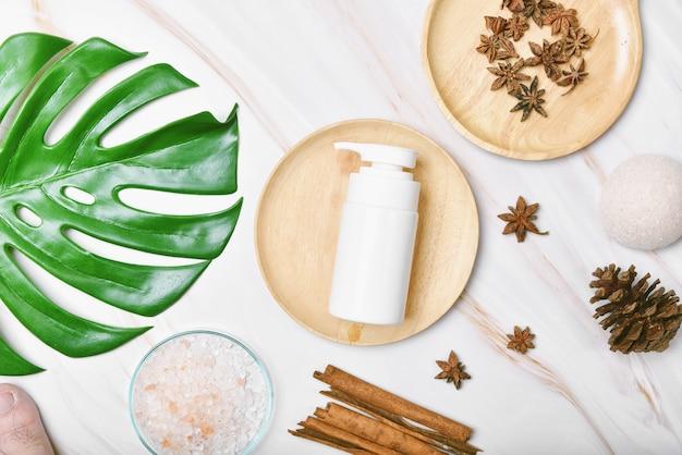 Naturalny produkt kosmetyczny do pielęgnacji skóry z olejem z przypraw, pojemniki na butelki z pompką kosmetyczną, opakowania z zielonymi liśćmi natury, pusta etykieta dla makiety marki ekologicznej spa, ziołowa zdrowa pielęgnacja skóry.