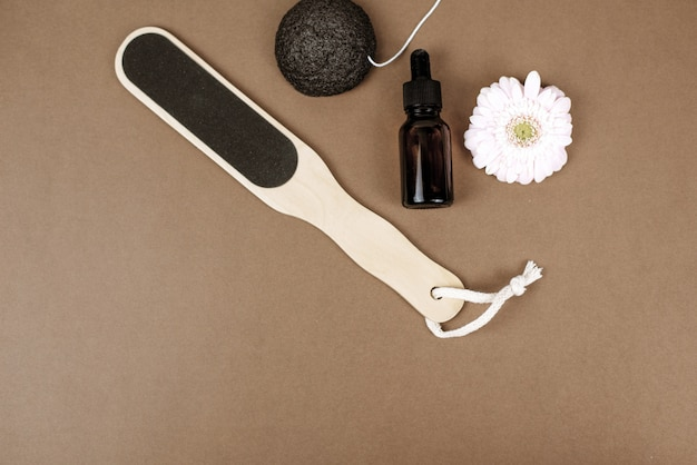 Naturalny pumeks do złuszczania skóry na brązowym tle obok kwiatu i serum nawilżającego