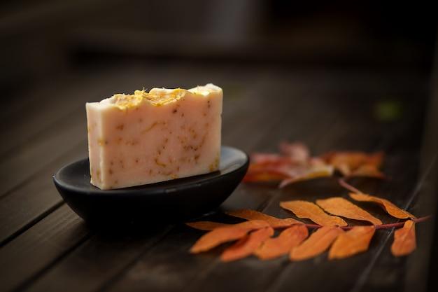 Naturalny ręcznie robiony mydło przeciw jesień liściom i drewnianemu tłu, zamyka up, boczny widok