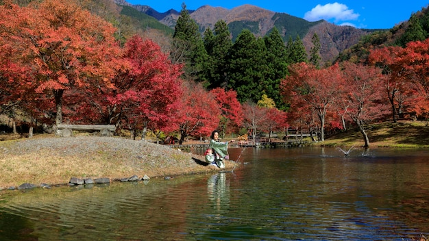 Naturalny rzeka park i małe kobiety jest ubranym kimono w jesień liściach japan