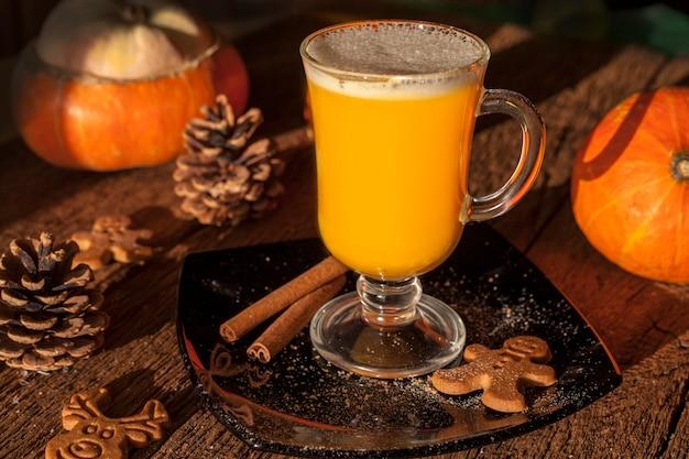 Naturalny sok dyniowy, skład szklanki soku na tle dyni, na drewnianym stole