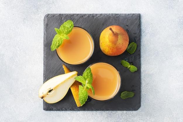 Naturalny sok gruszkowy w szklanym kubku. soczyste dojrzałe gruszki i liście mięty. widok z góry stojak łupkowy, jasne tło betonowe.