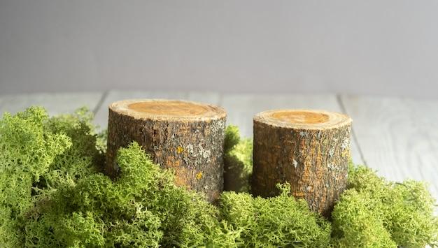 Naturalny styl. drewniane podesty lub stojaki ekspozycyjne z zielonym mchem na szarym stole. martwa natura do prezentacji produktów. .
