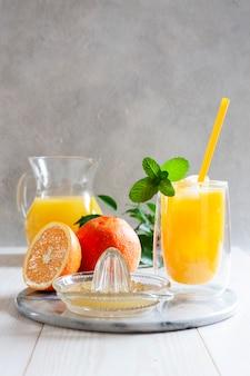 Naturalny świeżo wyciśnięty sok pomarańczowy z lodem i miętą w szklance
