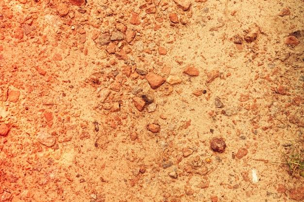 Naturalny tło piasek i kamienie na plaży.