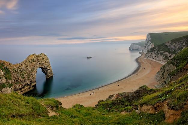 Naturalny wapień łuk durdle door na jurajskiej linii brzegowej dorset w anglii o zachodzie słońca