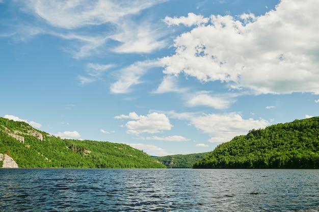 Naturalny widok na zielone pola na pierwszym planie i góry klifów i wzgórz w tle w słoneczny letni dzień.