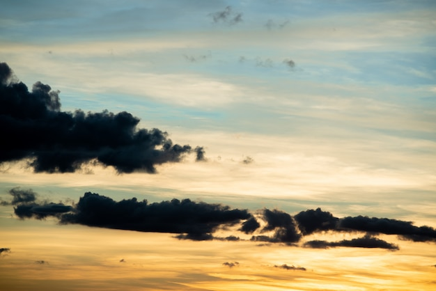 Naturalny wschód słońca zachód słońca nad polem lub łąką. jasne dramatyczne niebo i ciemna ziemia.
