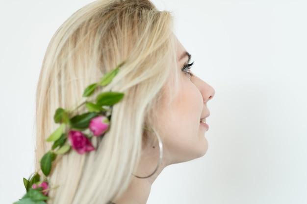 Naturalny wystrój włosów. blond dziewczyna ubrana w świąteczne akcesoria świeży kwiat