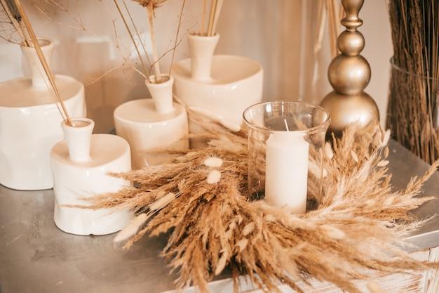 Naturalny wystrój wnętrz, stół, świeczniki ze świecami i suchymi ziołami
