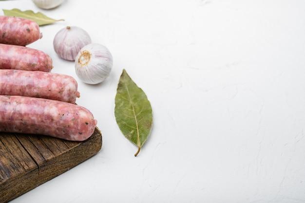 Naturalny zestaw kiełbas surowych, na białym tle kamiennego stołu, z miejscem na tekst