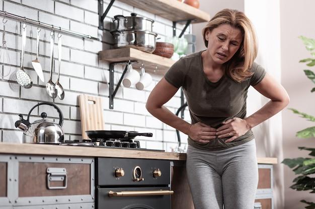 Natychmiastowy ból brzucha. blond kobieta w koszulce z silnym i natychmiastowym bólem brzucha