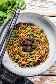 Natychmiastowy makaron ramen z kolendrą i tofu w żeliwnym naczyniu. danie wegetariańskie. białe drewniane tła. widok z góry