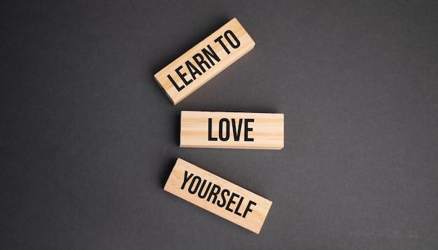 Naucz się kochać siebie słowem napisanym na drewnianym bloku. obiektywny tekst na stole, koncepcja.