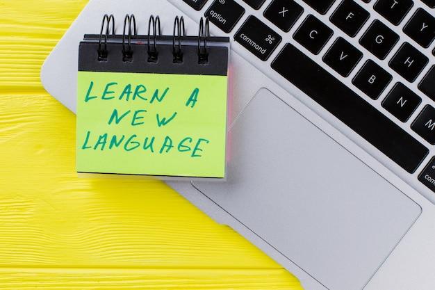 Naucz się nowej koncepcji języka. widok z góry laptopa na żółtym drewnie.