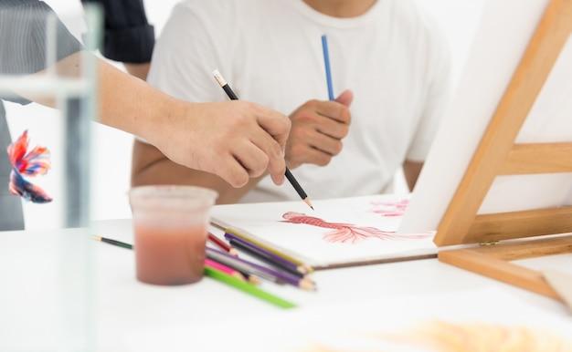 Naucz się rysować ryby. szkicuj, maluj i koloruj na papierze.