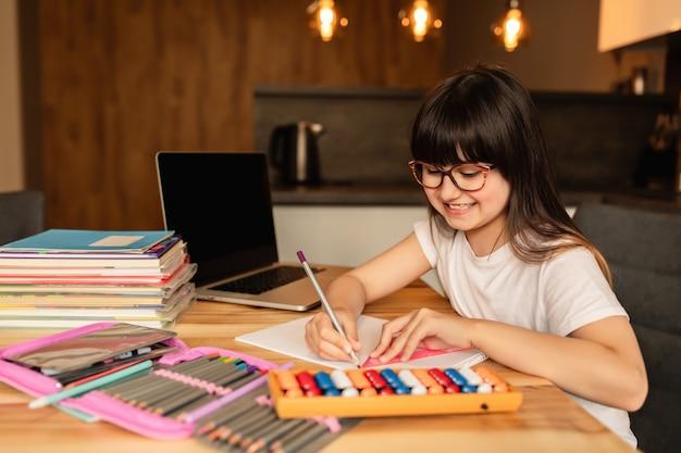Nauczanie domowe. nauka online. uczennica odrabia lekcje w domu. edukacja domowa. kształcenie na odległość