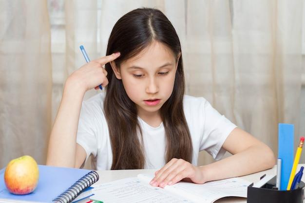 Nauczanie na odległość edukacja online zamyślona uczennica uczy się w domu odrabia pracę domową