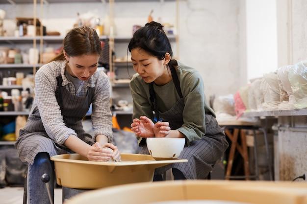 Nauczanie robienia glinianych wazonów na kole garncarskim