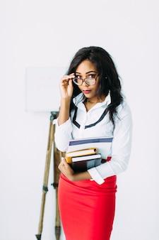 Nauczyciel afroamerykańskiej kobiety biznesu w okularach gospodarstwa książek i dokumentów