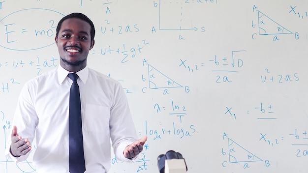 Nauczyciel afrykańskiego naukowca prowadzi zajęcia z nauk ścisłych za pomocą mikroskopu w klasie. koncepcja dnia szczęśliwego nauczyciela