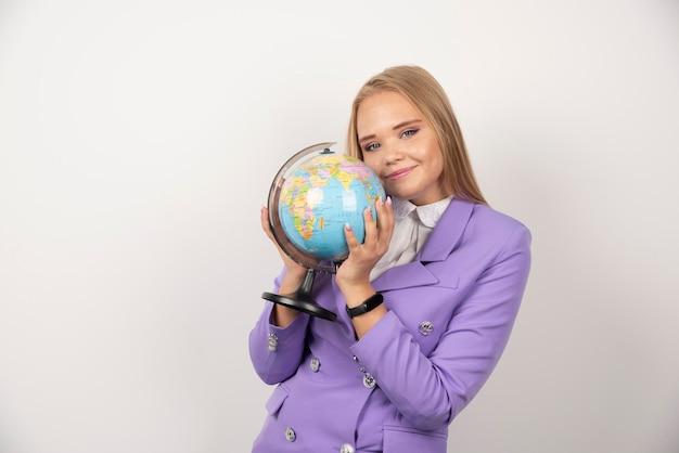Nauczyciel blondynka trzyma kulę ziemską na białym tle. wysokiej jakości zdjęcie