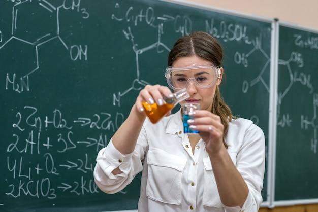 Nauczyciel chemii przeprowadza eksperyment z płynami w kolbie wyjaśnia uczniom nowy temat
