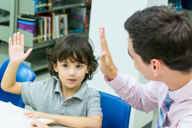 Nauczyciel człowiek i dziecko uczeń uczyć się z książki na tle półki