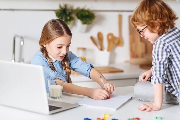 Nauczyciel domowy. urocza inteligentna ładna dama używa specjalnych plastikowych cyfr, wyjaśniając swojemu młodszemu bratu podstawowe arytmetyki, podczas gdy ona uważnie ją obserwuje i siedzi przy bajce obok niej