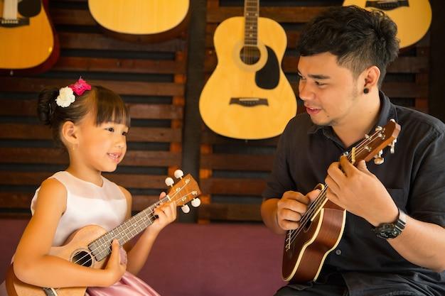 Nauczyciel gry na gitarze ukulele uczy muzyki w szkole