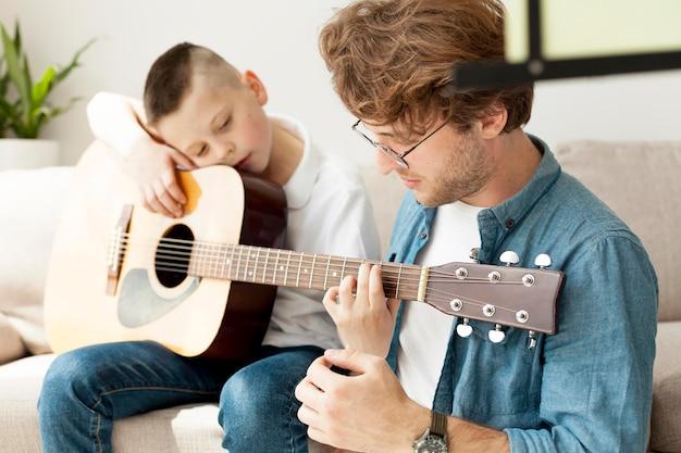 Nauczyciel i chłopiec uczą się gry na gitarze