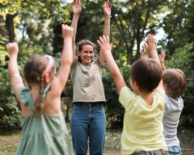 Nauczyciel i dzieci, ćwiczenia na świeżym powietrzu