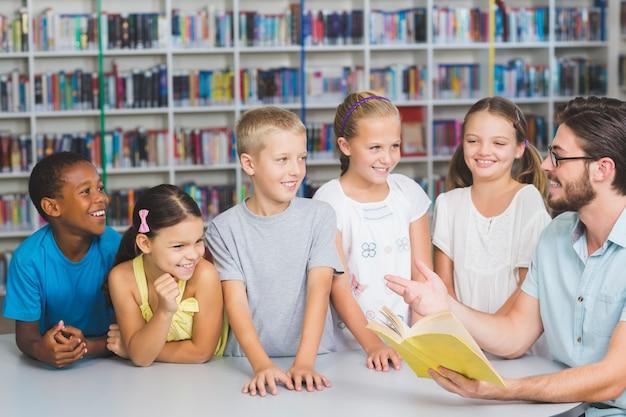 Nauczyciel i dzieci, czytanie książki w bibliotece
