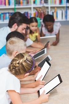 Nauczyciel i dzieci leżące na podłodze za pomocą cyfrowego tabletu w bibliotece