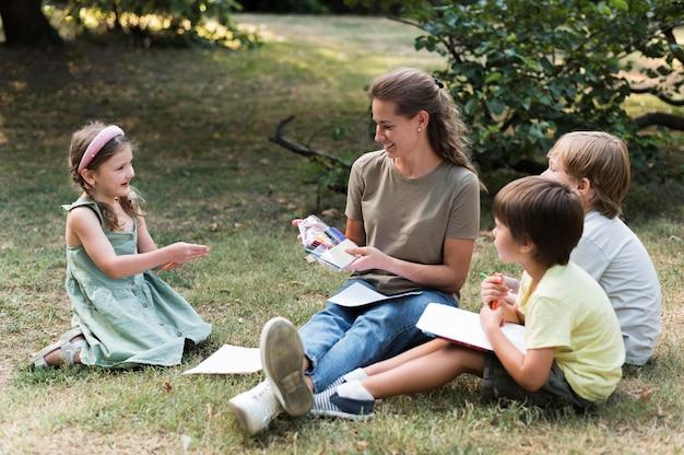 Nauczyciel i dzieci siedzą na trawie