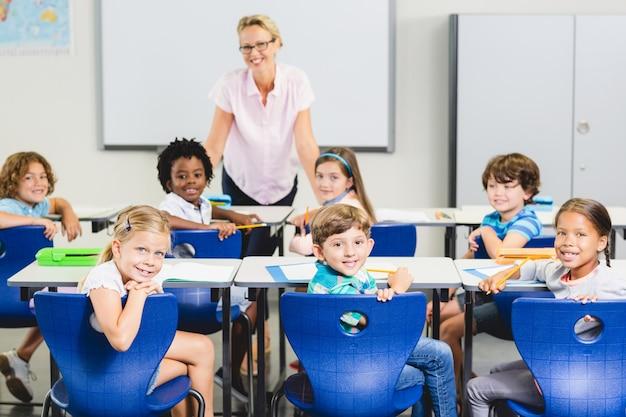 Nauczyciel i dzieci uśmiechając się w klasie