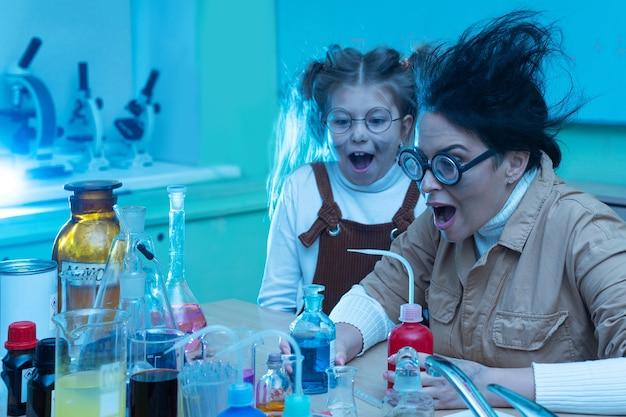 Nauczyciel i mała dziewczynka podczas lekcji chemii mieszają chemikalia
