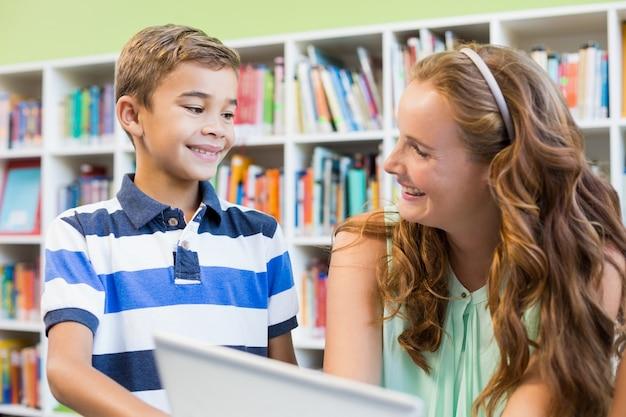 Nauczyciel i szkolna chłopiec używa laptop w bibliotece