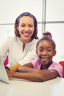 Nauczyciel i uczennice za pomocą cyfrowego tabletu w klasie