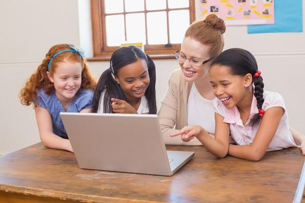 Nauczyciel i uczniowie patrząc na laptopa