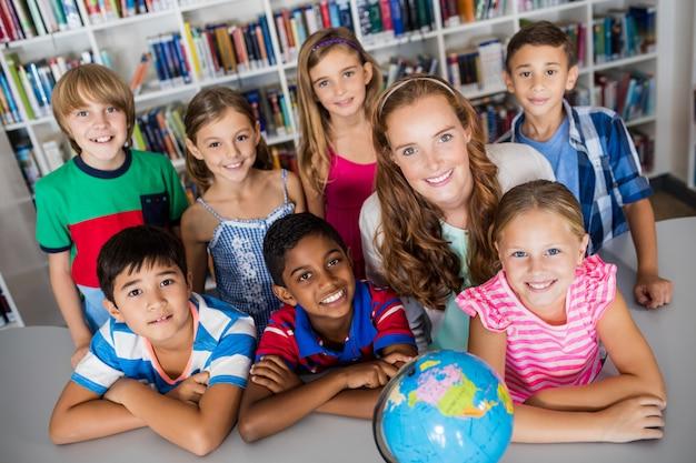 Nauczyciel i uczniowie pozowanie z globu