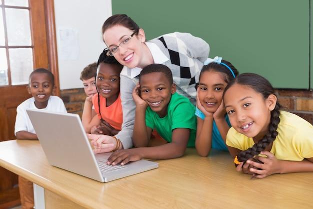 Nauczyciel i uczniowie pracujący na laptopie