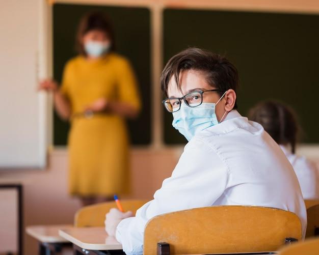 Nauczyciel i uczniowie z maską