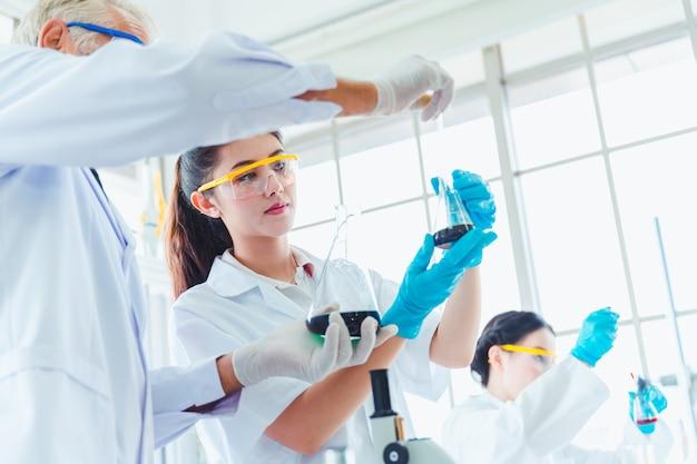 Nauczyciel i zespół studentów pracujących z chemikaliami w laboratorium