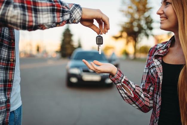 Nauczyciel jazdy przekazuje klucze studentce