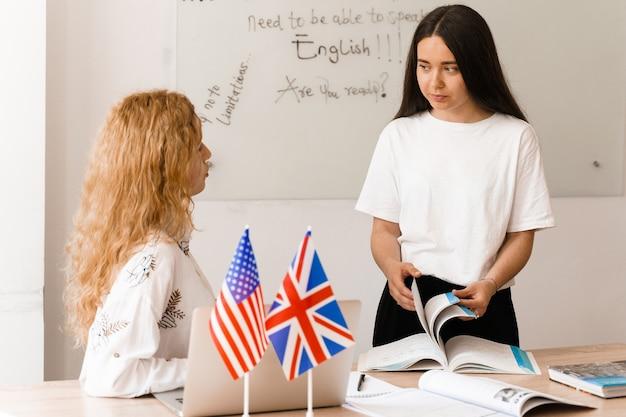 Nauczyciel języka angielskiego pyta ucznia w białej klasie