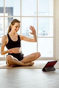 Nauczyciel jogi prowadzący wirtualną lekcję jogi w domu podczas wideokonferencji