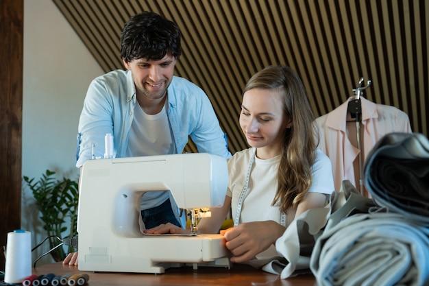 Nauczyciel mężczyzna pomaga studentce mody uczącej się korzystać z maszyny do szycia