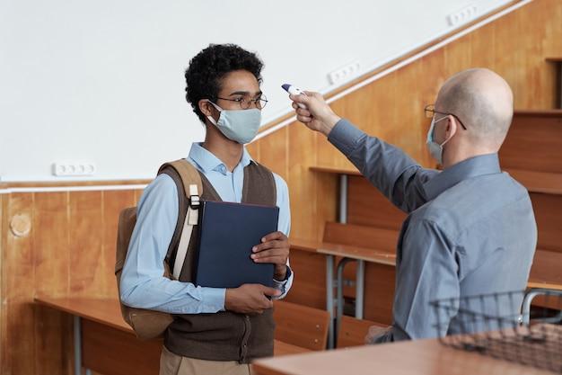 Nauczyciel mierzący temperaturę ciała ucznia w masce w klasie