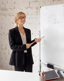 Nauczyciel na tablicy wyjaśniającej